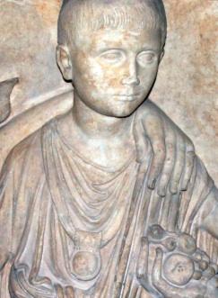 """Niño romano, con su bula al cuello. La """"bulla"""" era un amuleto que el niño llevaba hasta los 16 años en que hacíase ciudadano romano. Tenía por objeto conjurar las influencias malignas y mostrar un signo de que el portador de la bula era religiosa y legalmente inutilizable como `sexualmente penetrable por vía rectal."""